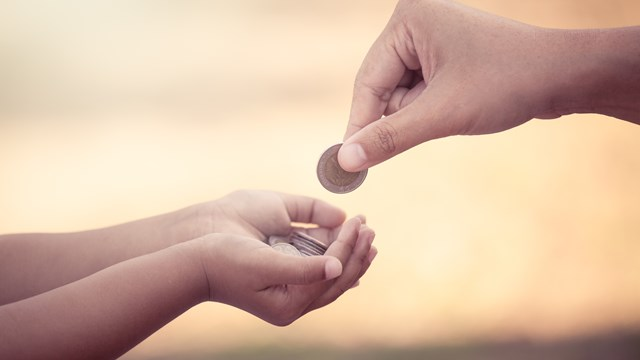Mother gives coins to children who save money