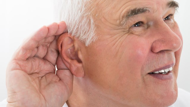 older man holding his hand to his ear to hear better