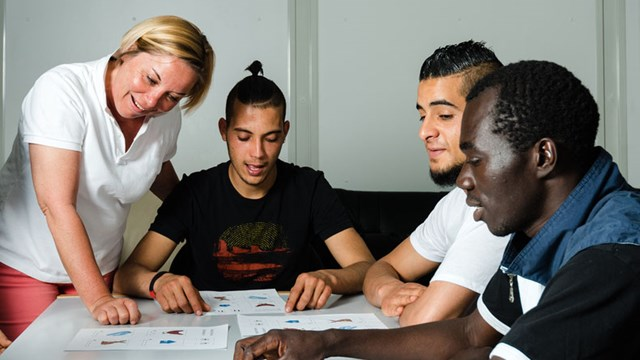 Language training for refugees in a German camp: A female German volunteer is teaching young refugees.