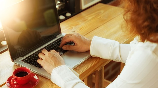 Woman sitting at laptop and writing.
