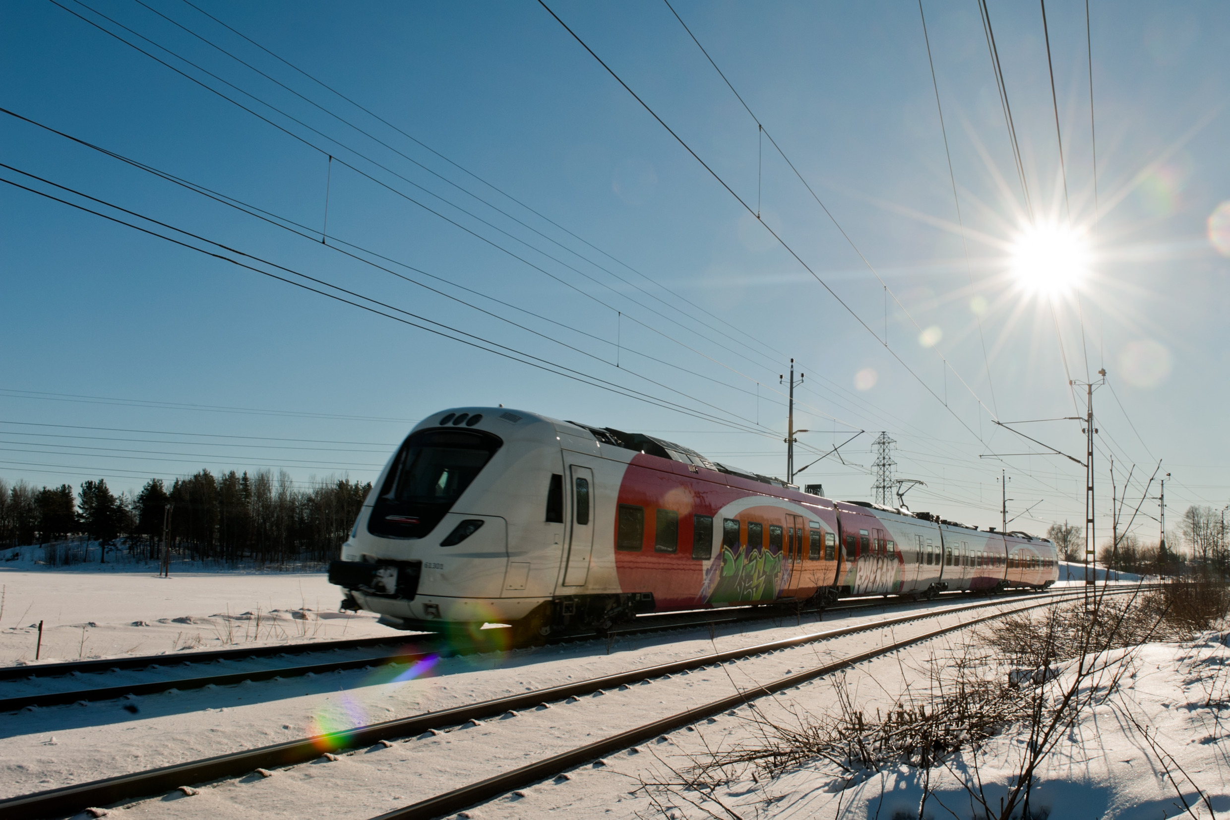 Electric train travelling through snowy Swedish country side in Östergötland.
