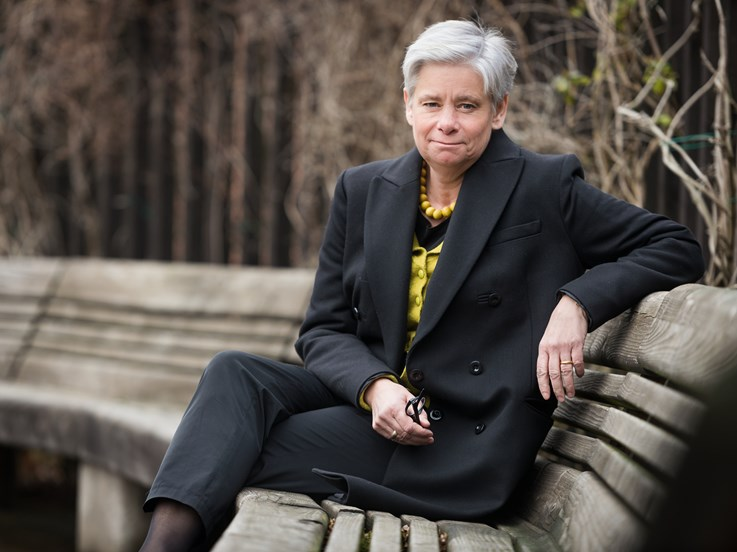 Linköping University's Vice-Chancellor Helen Dannetun, sitting on a bench outside in autumn for a portrait photograph.