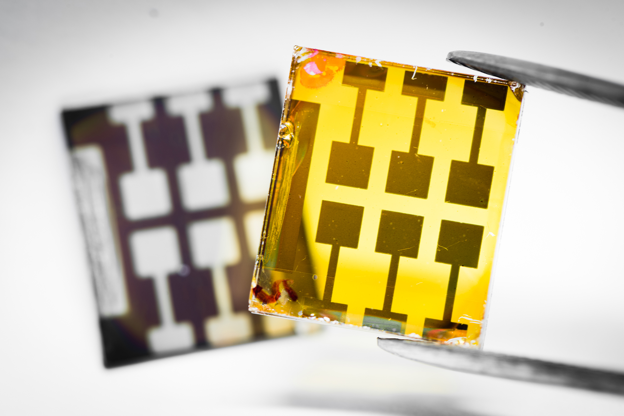 The lead-free double perovskite solar cells (yellow, in the front) compared with the lead-based device (dark, in the background). The next step is tune the color of the double perovskites into dark, so that they can absorb more light for efficient solar cells.