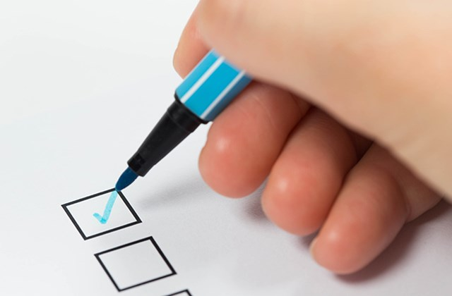A paper and pen on a form with checklist checked