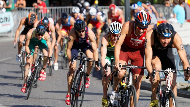 Large group of muscular cycling triathlon competitors