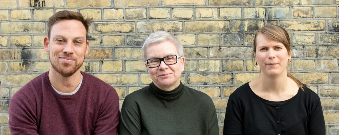 Portrait of the three editors in front of a yellow brick wall.