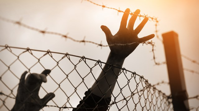 Hands by fence. Photo: iStockphoto