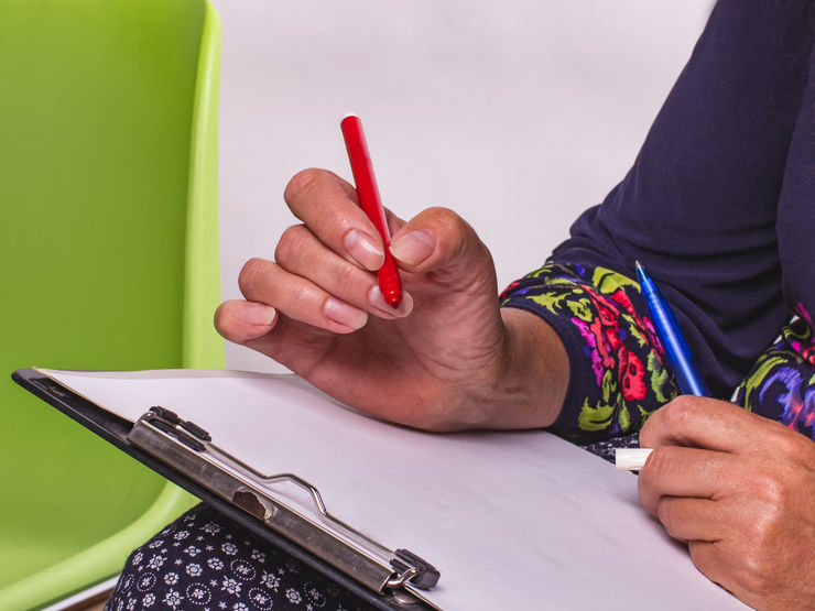 Adult woman in pattern dress with red felt pen writing in a notebook.