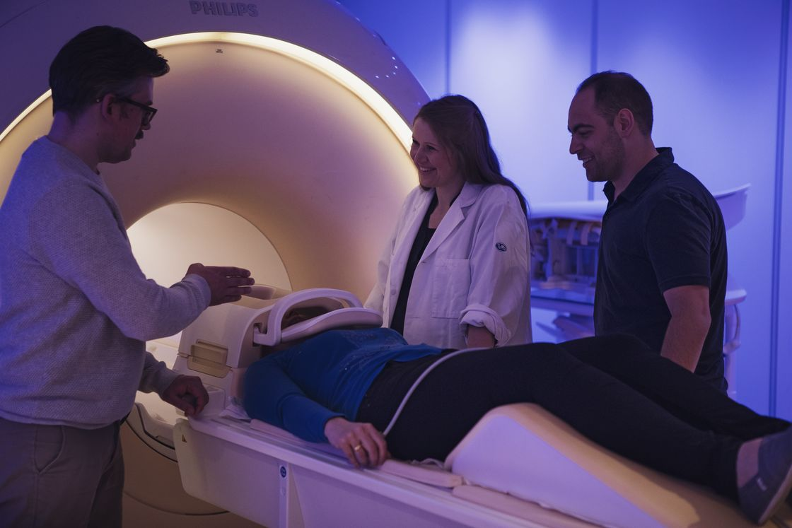 Three researchers are standing around a patient in an MRI.