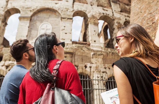 Tourists with guide in front of Coliseum in Rome.
