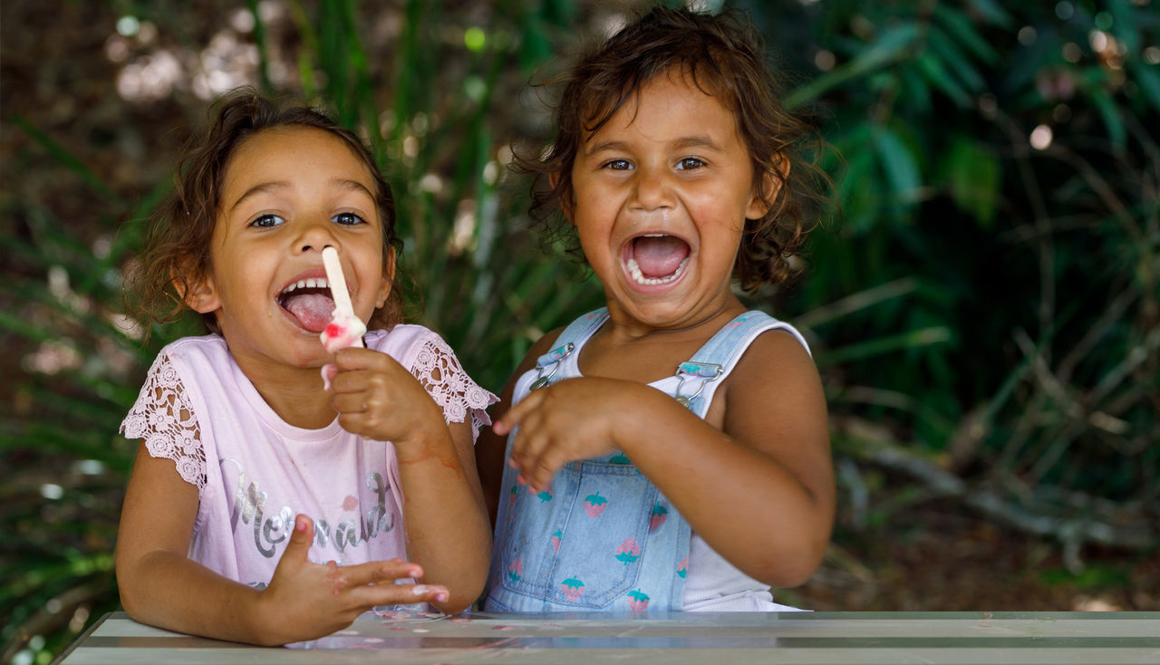 Two Young Australian Aboriginal Girls eating an Ice Cream at park at Lismore, NSW, Australia
