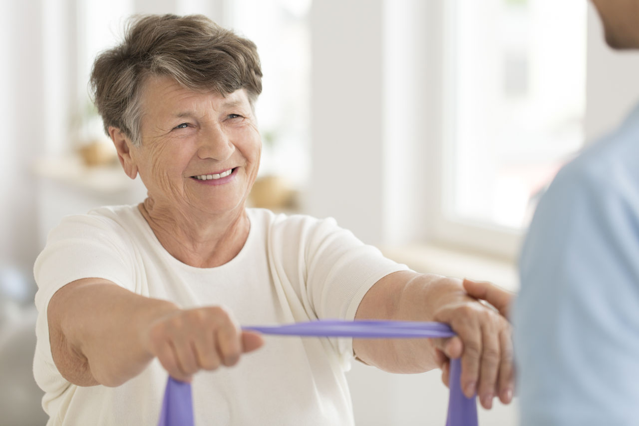 Smiling senior woman doing strength exercise with elastic tape during rehabilitation