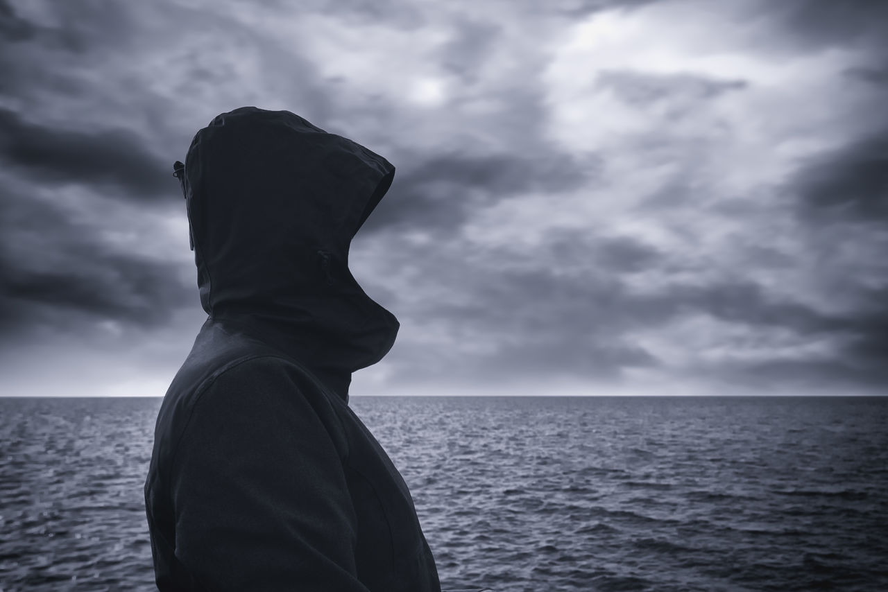 Faceless hooded person looking into distance at horizon over the sea water on cold windy winter day, anticipating unpredictable future