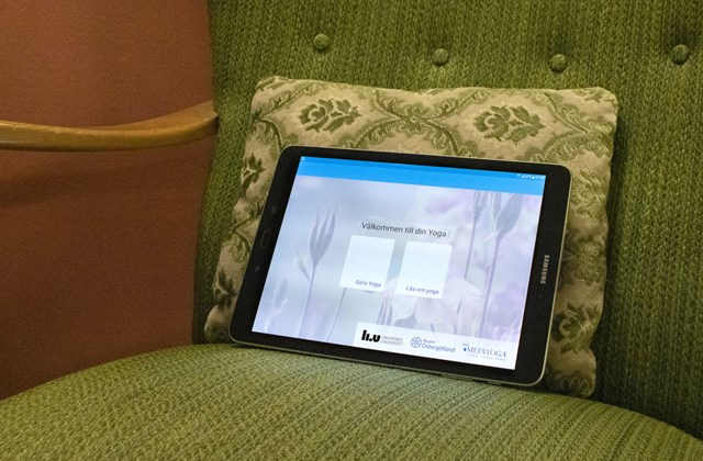 Tablet placed standing on the cushion of an armchair.