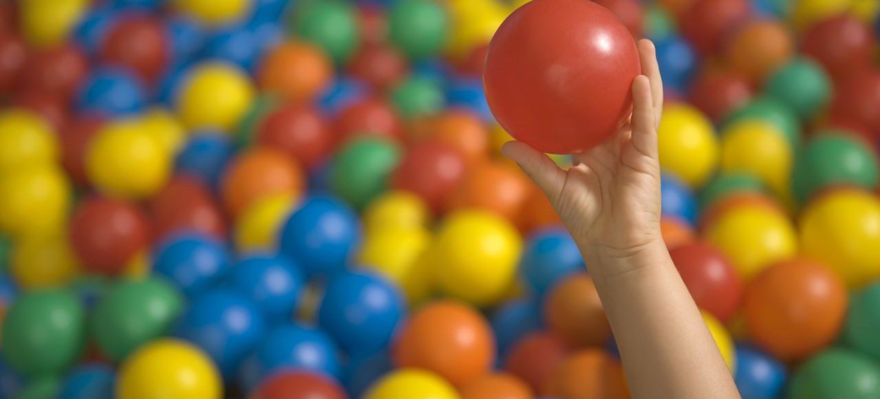 Close-up of a child's hand holding a ball in a ball pool