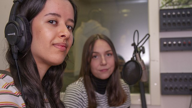 Two students at the control table in a sound studio.