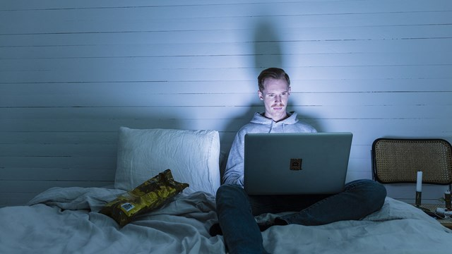 Man sits on a bed with laptop