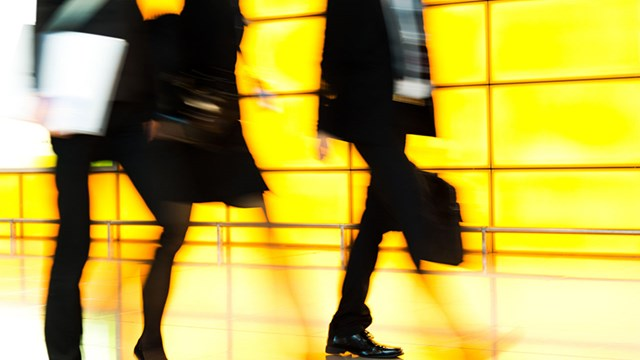 Abstract image with walking people - bright yellow wall