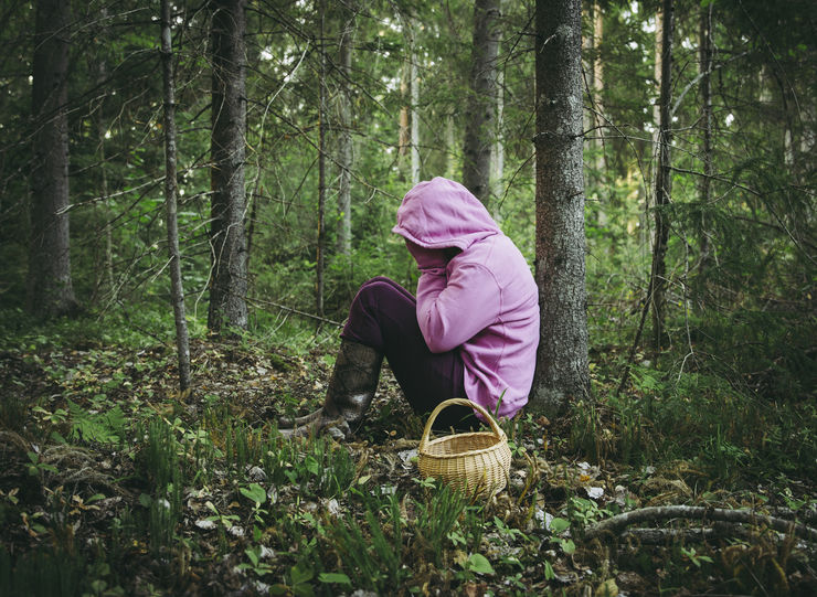 Confused person went to mushroom picking and got lost in the forest, disoriented scared and confused, northern Europe, sit under tree. Person lost in nature concept. Wearing bright colorful clothing.