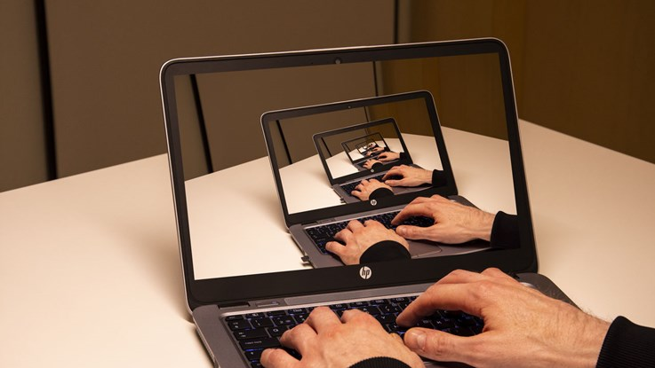 Hands writing on a laptop with the same image shown on the laptop screen.