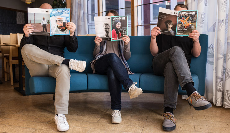 Three people sit in a sofa holding magazines so that they cover their faces