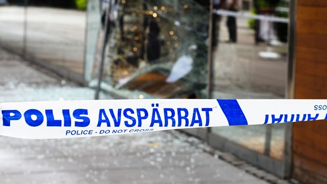 Police barricade in front of a smashed window