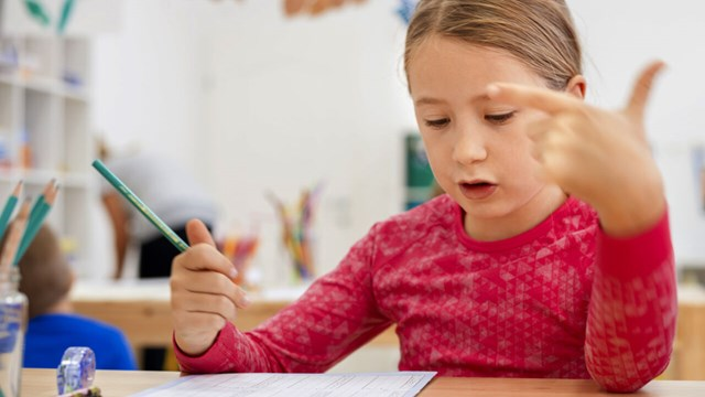 Schoolgirl siting in classroom and counting using her fingers while writing in her notebook.