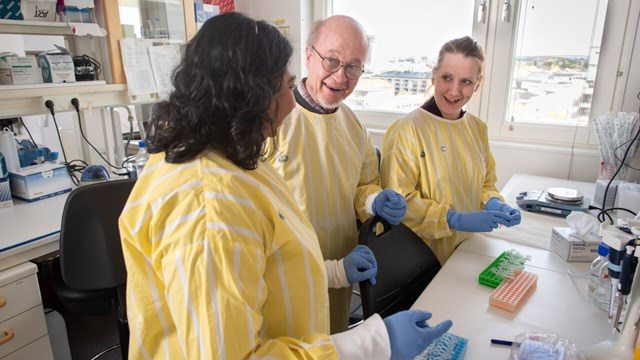 Professor Jorma Hinkula have a discussion with two PhD students in the laboratory.