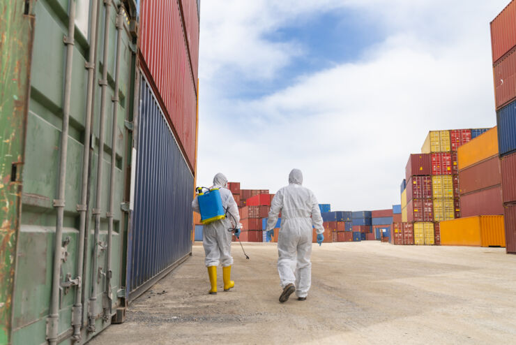 People wearing protective suits spray disinfectant chemicals on the cargo container to prevent the spreading of the coronavirus.