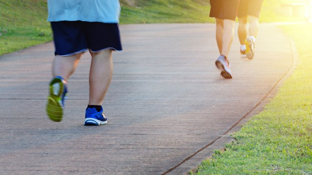 Fat man jogging, catching up with thin men. Low angle view of runners running in park. Blurred feet motion group of runners, Fitness and healthy lifestyle, outdoor sports activity. Copy space.