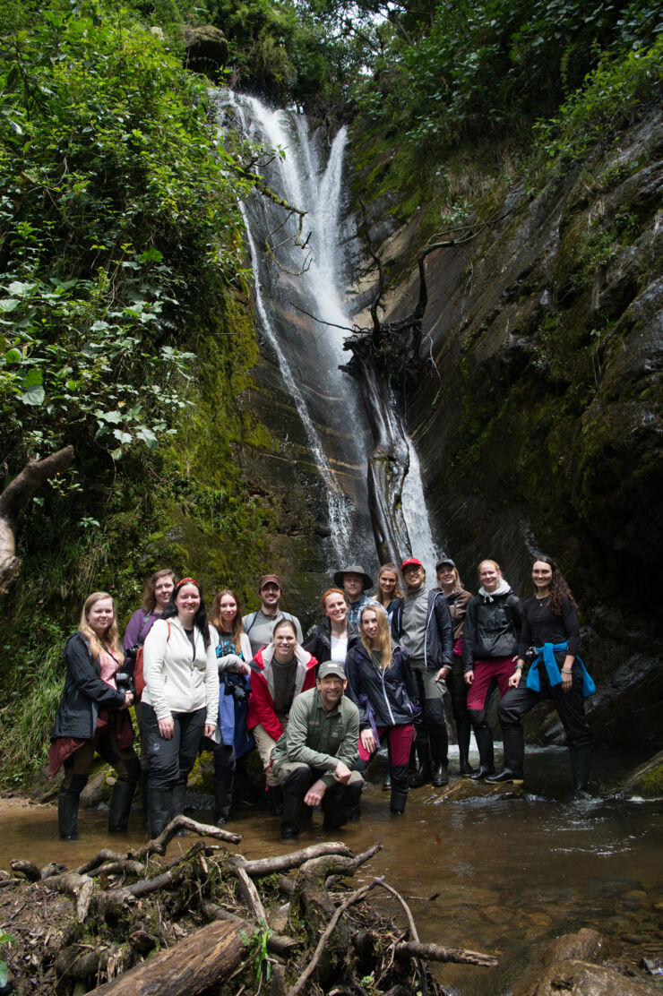 A group of people in front of a waterfall in the rainforest