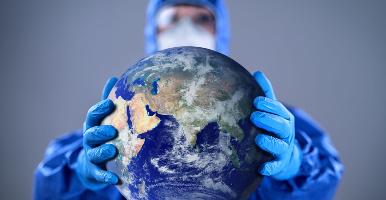 Doctor wearing highly protective suit and holding globe in her hands
