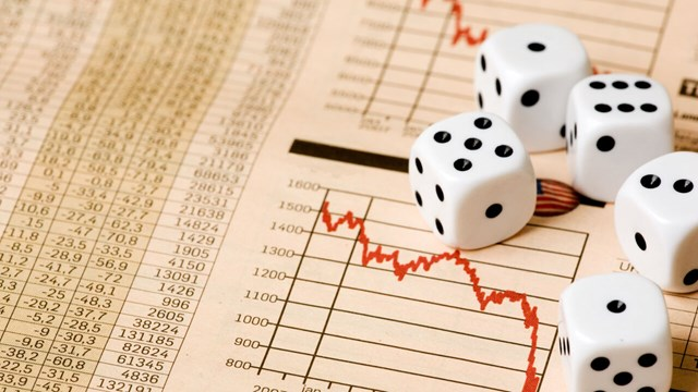 Dices lying on paper on stock market prices.