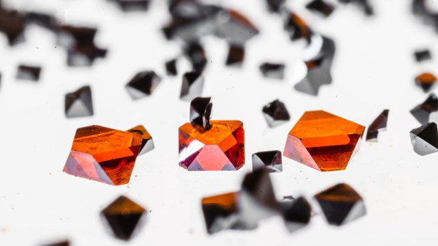 Perovskites, similar to black and red crystals, lies on a light table.