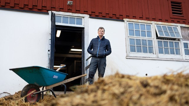Uno Wennergren in front of a stable and a pile of fertiliser.