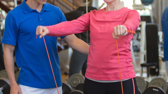 A physiotherapist in a blue shirt is standing to the left of a woman in a pink shirt doing an exercise. You can not see their faces.
