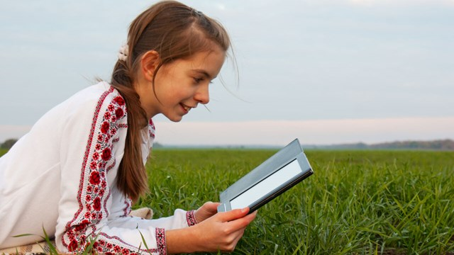 Teen girl with electronic book laying on grass at field