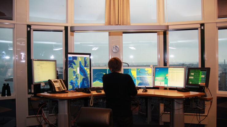 Women infront of computer screens at sea traffic hub.