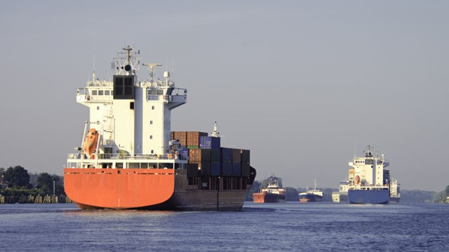 Multiple cargo ships meet in a narrow strait.
