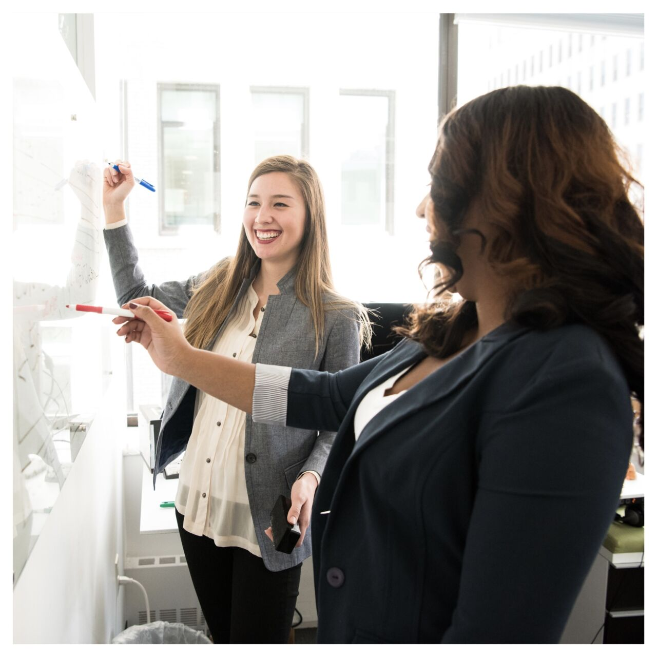 Two laughing women standing and writing on whiteboard.