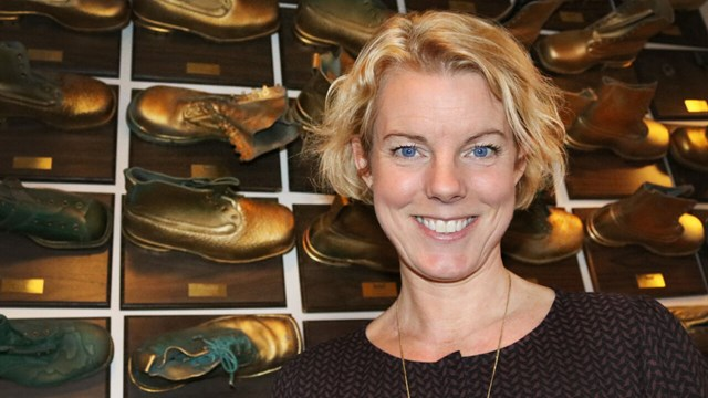 Woman by a wall full of golden-coloured shoes.