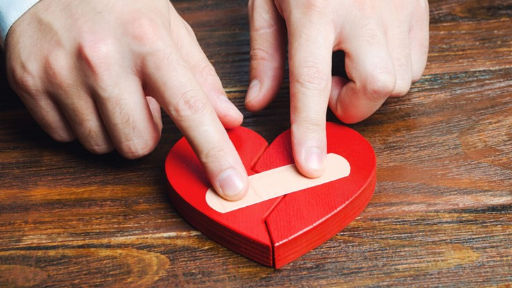 A pair of hands are putting a plaster on a red, flat wooden heart.