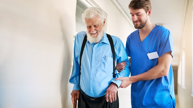 Male nurse helping older man to walk