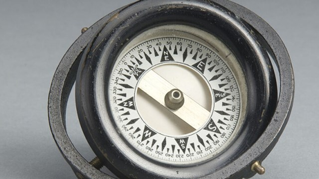 Older compass against a grey background.