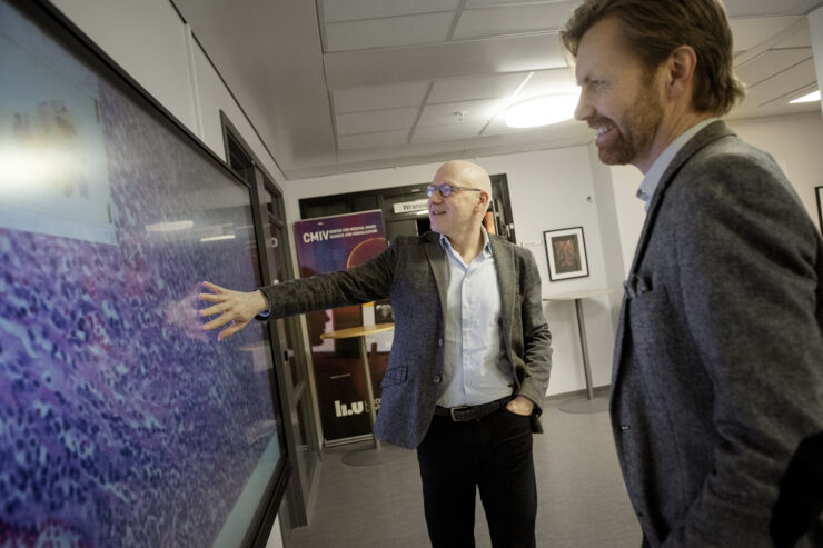Två forskare diskuterar en digital bild på vävnadsprov.