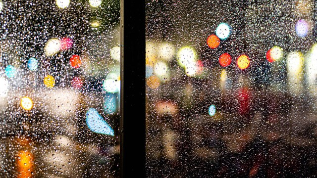 Photo on a rainy lit up street, taken through a window.