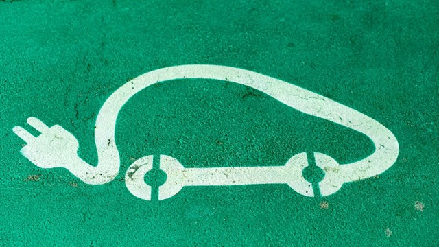 Symbol for electric car on green background.