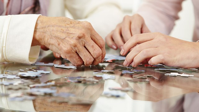 Close up on two people with a puzzle. One older person and one young.