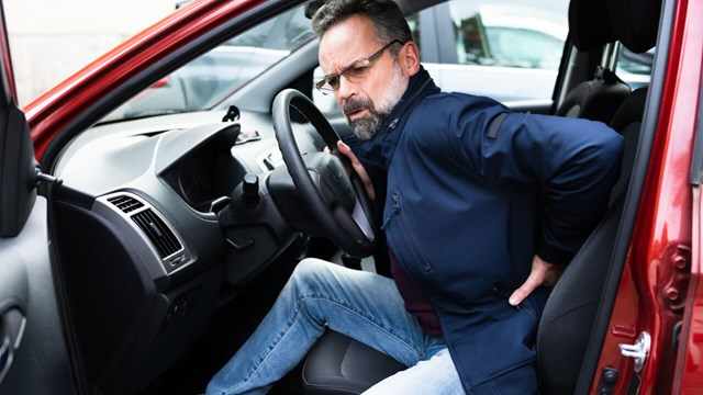 A man is stepping out of a car, holding his back and the facial expression shows discomfort.